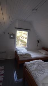 A bed or beds in a room at Rörvik Stugor