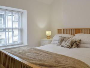 A bed or beds in a room at Uppergate Cottage