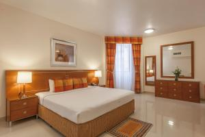Een bed of bedden in een kamer bij Golden Sands Hotel Apartments