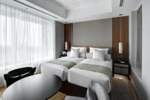 A bed or beds in a room at Ascott Marunouchi Tokyo