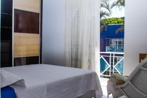 A bed or beds in a room at Apto a 70 metros da praia, Piscina e 02 vagas de Garagem