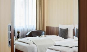 A bed or beds in a room at Living Hotel Düsseldorf
