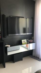Una televisión o centro de entretenimiento en Apartamento Super Aconchegante