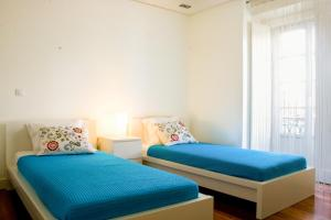 En eller flere senge i et værelse på HolidayLovers Chiado Deluxe