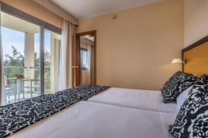 Een bed of bedden in een kamer bij Zafiro Tropic