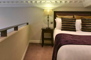 A bed or beds in a room at Fraser Suites Queens Gate