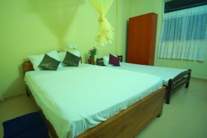 A bed or beds in a room at Bentota Homes