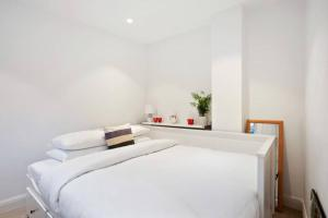Een bed of bedden in een kamer bij Charming 2 Bedroom Flat with Garden in Finsbury Park