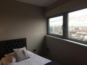 A bed or beds in a room at High View Serviced Apartments