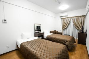 A bed or beds in a room at COZY STAY IN URASOE