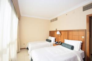 A bed or beds in a room at Al Rawda Arjaan by Rotana, Abu Dhabi