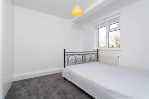 A bed or beds in a room at Lovely Wimbledon Family Apartment