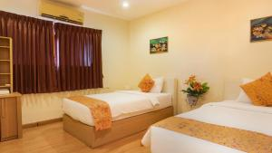 A bed or beds in a room at Phuket Center Hotel