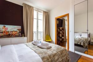 A bed or beds in a room at CMG Trocadéro - Victor Hugo