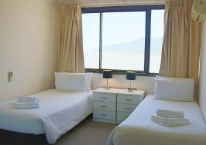 A bed or beds in a room at Cairns Aquarius