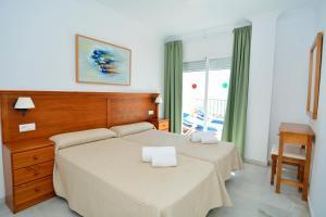 Una cama o camas en una habitación de Apartamentos HC Burriana Playa