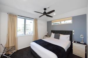 A bed or beds in a room at Pavilion Beachfront Apartments