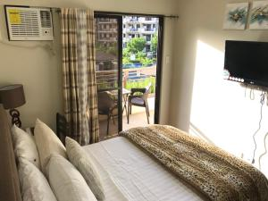 A television and/or entertainment center at MaRoy Suites at Asteria Residences (Near NAIA with free Parking+Fiber Internet)