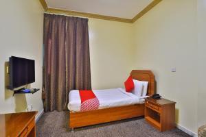 A bed or beds in a room at OYO 150 Al Hamra Palace Al Aswaq