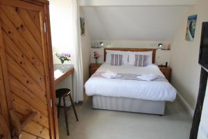 A bed or beds in a room at Houndapitt Cottages