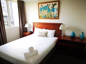 A bed or beds in a room at Abbey On Roma Hotel & Apartments