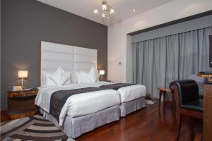 A bed or beds in a room at City Premiere Hotel Apartments