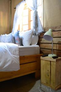 A bed or beds in a room at Nxabii Cottages