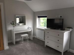 Una televisión o centro de entretenimiento en Stoneybridge Lodge