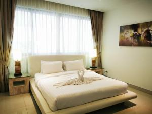 A bed or beds in a room at Sansuri Residence Apartments