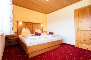 A bed or beds in a room at Landhotel Hinteraigengut