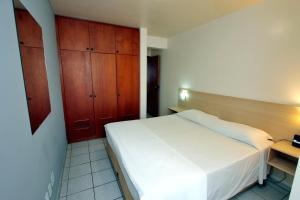 A bed or beds in a room at Belluno Apart Hotel