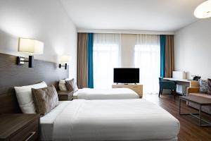 Un ou plusieurs lits dans un hébergement de l'établissement Ramada Hotel & Suites by Wyndham Novosibirsk Zhukovka
