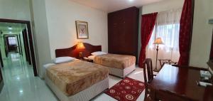 سرير أو أسرّة في غرفة في أيفوري للشقق الفندقية