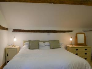 A bed or beds in a room at Oak Barn Cottage