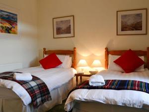 A bed or beds in a room at Inverchroskie Cottage