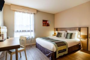 A bed or beds in a room at Comfort Suite Rive Gauche Lyon Centre