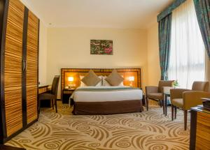 A bed or beds in a room at Al Majaz Premiere Hotel Apartments