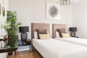 A bed or beds in a room at Canaan Boutique Apartments Madrid