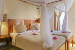 A bed or beds in a room at Jambiani Villas