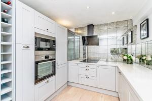 A kitchen or kitchenette at The Racecourse Apartments- Luxury and location