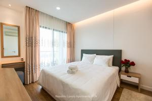 A bed or beds in a room at Republic Apartments Saigon Airport