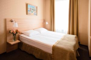 A bed or beds in a room at Nevsky Grand Apartments