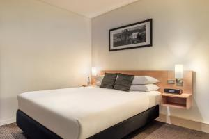 A bed or beds in a room at ibis Melbourne Hotel and Apartments