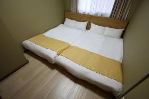 เตียงในห้องที่ Lumiere Yuhigaoka
