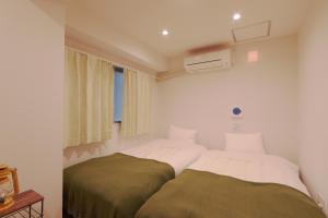 A bed or beds in a room at V.Close to Shinjuku Kabukicho/Korean Town/FrWIFI D