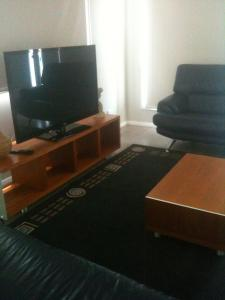 A television and/or entertainment center at Denman Serviced Apartments