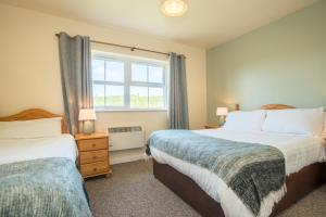 A bed or beds in a room at Doherty Farm Holiday Homes