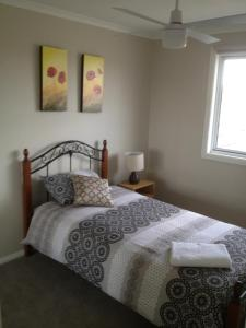 A bed or beds in a room at Denman Serviced Apartments