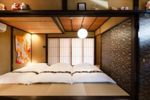 A bed or beds in a room at Machiya Vacation House YululY