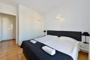 A bed or beds in a room at Apartamentos San Antonio Beach